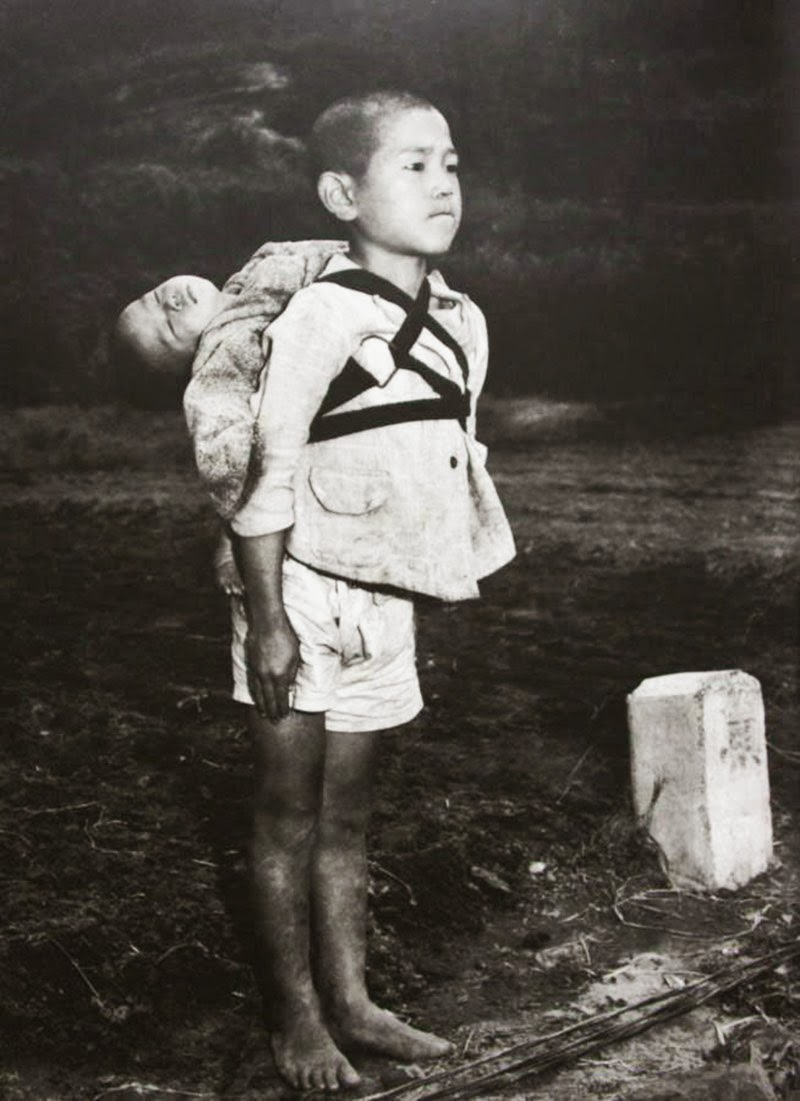 a-japanese-boy-standing-at-attention-after-having-brought-his-dead-younger-brother-to-a-cremation-pyre-1945